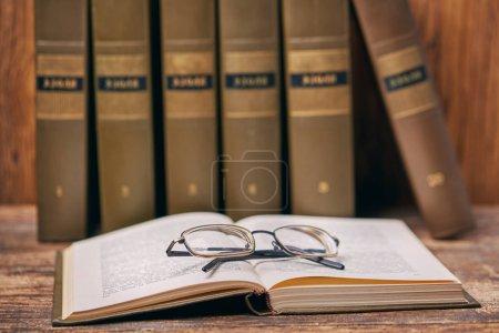 Photo pour Livre ouvert avec des verres sur la table. Concept éducatif - livres sur le bureau de l'auditorium - image libre de droit