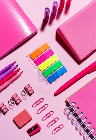 Photo pour Autocollants couleur, carnets roses, trombones, marqueurs, bande élastique et aiguiseur sur fond rose - image libre de droit