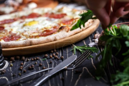 Photo for Cutlery near pizza and greenery. A fragment of pizza. Poster for Restaurants or pizzerias. Pizza on a black background - Royalty Free Image
