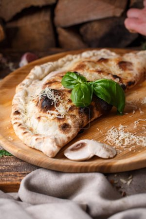Photo for Pizza Calzone folded in half is decorated with basil on the background of firewood. Poster for Restaurants or pizzerias - Royalty Free Image