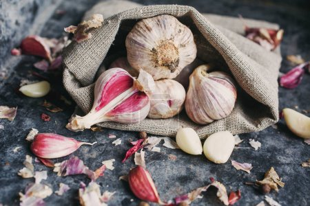 Photo for Peeled garlic cloves. Garlic scattered out of the sack - Royalty Free Image