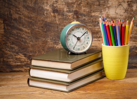 Photo for An old clock on the books on the table at the student. Education concept - books on the desk in the auditorium. On a wooden background - Royalty Free Image