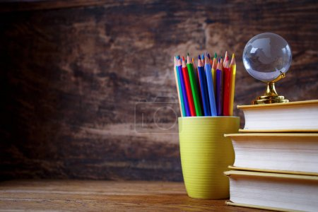 Photo for Globe on books and pencils on a student table. School objects for students. Education and wisdom concept. On a wooden background - Royalty Free Image