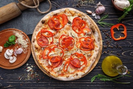 Photo for Original pizza with sausage, mushrooms, bulgarian pepper and cheese. Pizza on a black wooden background among spices - Royalty Free Image