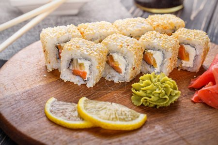 Photo for As package design element. Rolls of fish and cheese decorated with lemon slices - Royalty Free Image