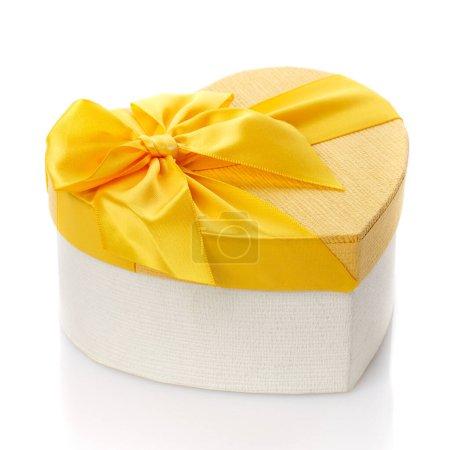 Photo pour Belle boîte cadeau en forme de coeur avec grand arc jaune. Isolé. Vue latérale. Concept de célébration de la Saint-Valentin. - image libre de droit