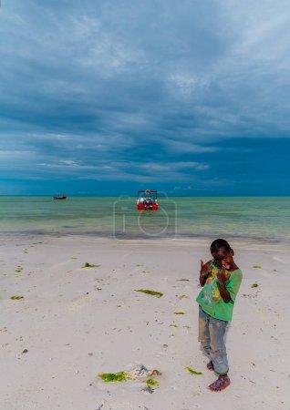 Photo pour Tanzanie, Zanzibar, 21 mars 2018. Un petit garçon africain se tient pieds nus sur le sable dans les vêtements déchirés et sales près de l'eau et un bateau à moteur contre. - image libre de droit