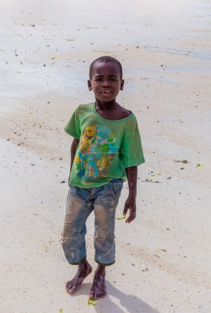 Photo pour Tanzania, Zanzibar, march 21, 2018. One small african boy stands barefoot on sand in torn and dirty clothes. - image libre de droit