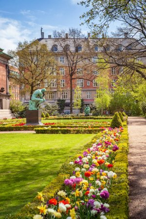 Urban scene with city park with flowers and monument in Copenhagen, denmark