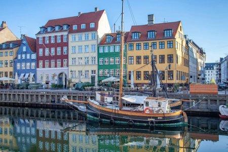 COPENHAGEN, DENMARK - MAY 6, 2018: boat and beautiful colorful buildings reflected in calm water of harbor, copenhagen, denmark