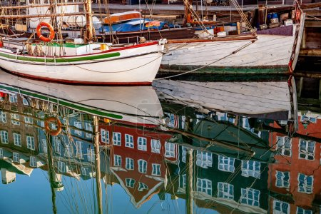 COPENHAGEN, DENMARK - MAY 6, 2018: historical buildings and boats reflected in calm water, copenhagen, denmark