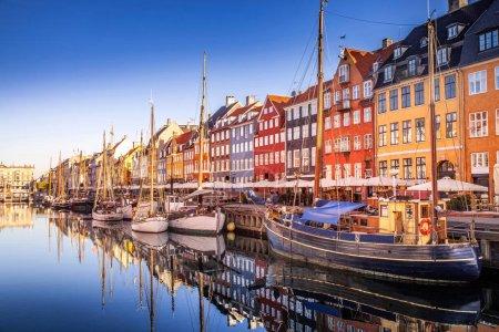 COPENHAGEN, DENMARK - MAY 6, 2018: picturesque view of historical buildings and moored boats reflected in calm water, copenhagen, denmark