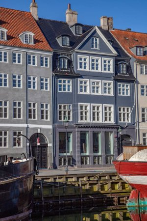 COPENHAGEN, DENMARK - MAY 6, 2018: beautiful historical buildings near water and moored boats in copenhagen, denmark
