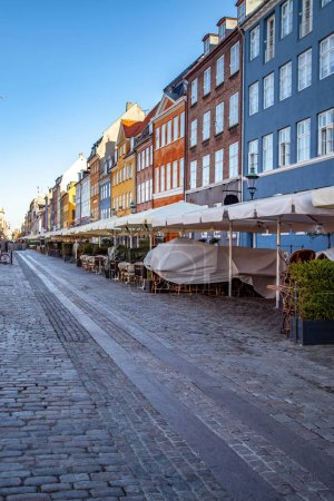 pavement and umbrellas at street cafe near beautiful colorful houses in copenhagen, denmark