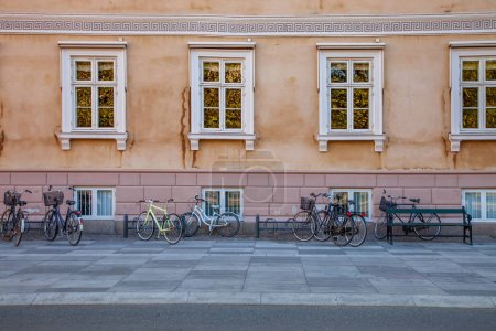 empty bench and bicycles parked near old house on street in copenhagen, denmark