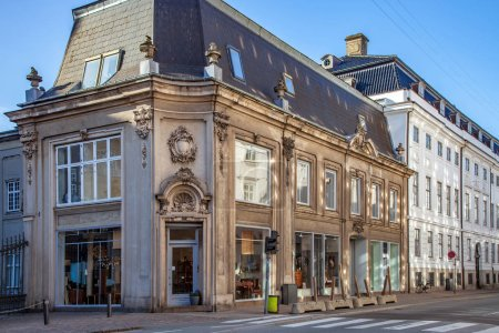 beautiful historical building with large windows and decorative sculptures on street in copenhagen, denmark