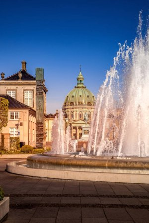 Photo for Beautiful fountain on empty square with historical buildings and church in copenhagen, denmark - Royalty Free Image