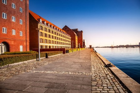 empty embankment near harbor and buildings at sunny day, copenhagen, denmark