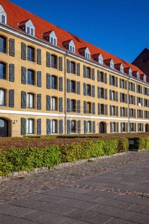 beautiful green bushes near historical building with open shutters in copenhagen, denmark