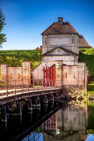 empty wooden bridge and gates with lanterns and old fortification structure reflected in water, copenhagen, denmark