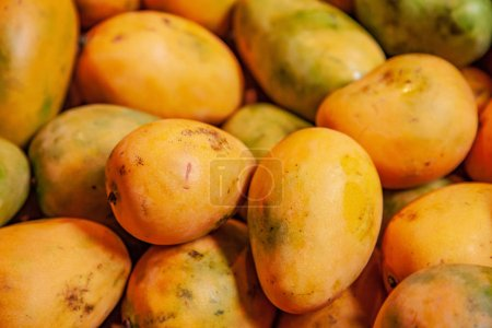 selective focus of pile of yellow mangoes