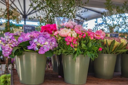 Close up view of buckets with hortensia and peonies on market place