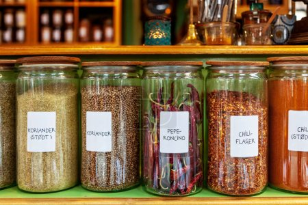 close up image of different spices in jars placed in row