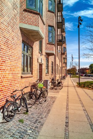 COPENHAGEN, DENMARK - MAY 6, 2018: cityscape with buildings and parked bicycles on empty street