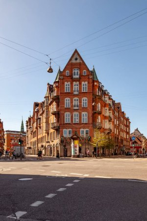 COPENHAGEN, DENMARK - MAY 6, 2018: cityscape with buildings and people walking on street in Copenhagen, Denmark