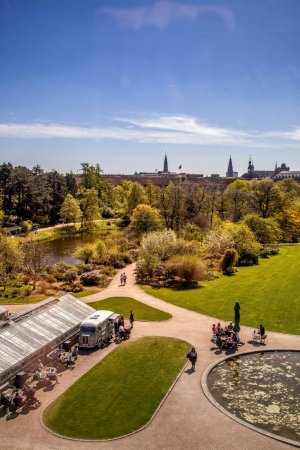 COPENHAGEN, DENMARK - MAY 6, 2018: aerial view of trees and pond in park and people sitting at tables in Copenhagen, Denmark