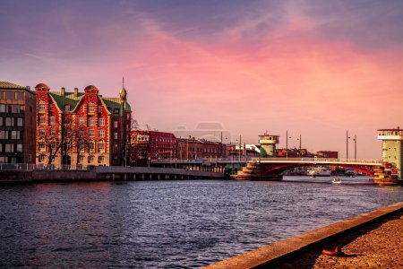 Photo for COPENHAGEN, DENMARK - MAY 6, 2018: scenic view of cityscape with river and bridge in foreground during sunset time - Royalty Free Image