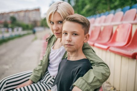 beautiful mother and son looking at camera while sitting together on stadium seats