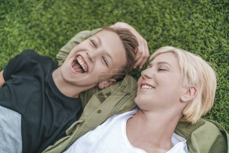 Photo for High angle view of happy mother and son laughing while lying together on grass - Royalty Free Image