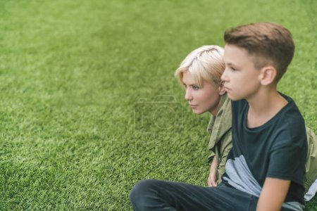 side view of beautiful mother and son looking away while sitting together on grass
