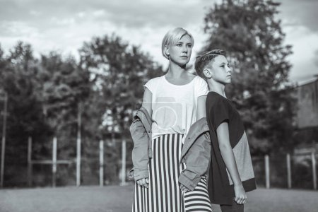 black and white photo of mother and son looking away while standing back to back in park
