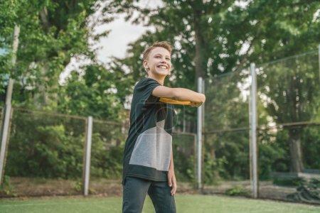 Photo pour Beau garçon souriant, jouant avec flying disc et regarder loin à l'extérieur - image libre de droit