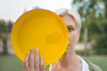 Photo pour Belle femme blonde maintenant jaune battant disque et regardant la caméra - image libre de droit