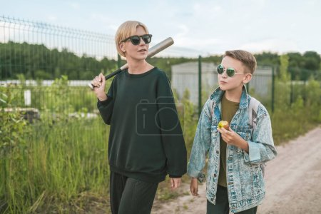 mother and son walking together on ground road, woman holding baseball bat and boy eating apple