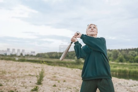 beautiful blonde woman playing with baseball bat and looking up at cloudy sky