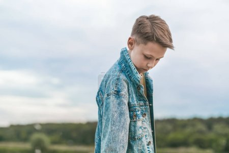 beautiful boy in denim jacket looking down at cloudy day