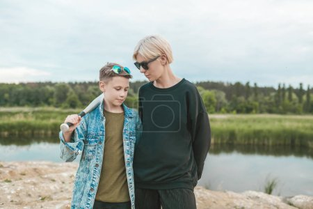 beautiful mother and son in sunglasses standing with baseball bat near lake