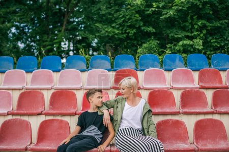 beautiful mother and son looking each other while sitting together on stadium seats