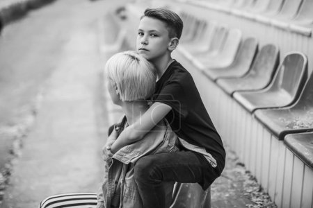 black and white photo of mother and son hugging on stadium