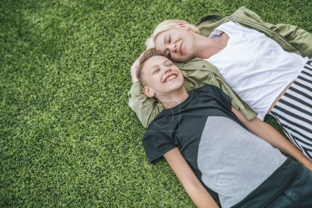 high angle view of happy mother and son laughing while lying together on green grass