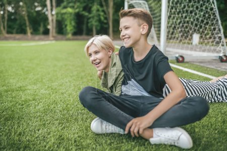 cheerful mother and son laughing and looking away while resting together on green lawn