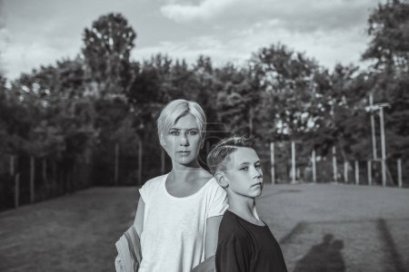 black and white photo of mother and son standing together on lawn
