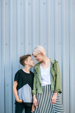 beautiful stylish mother and son looking at each other while standing together on street