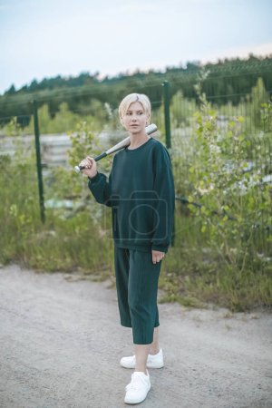 beautiful blonde woman holding baseball bat and looking away while standing on ground road near fence