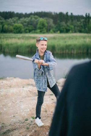 selective focus of smiling boy playing baseball with mother outdoors