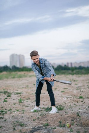 happy boy in denim jacket playing with baseball bat at cloudy day